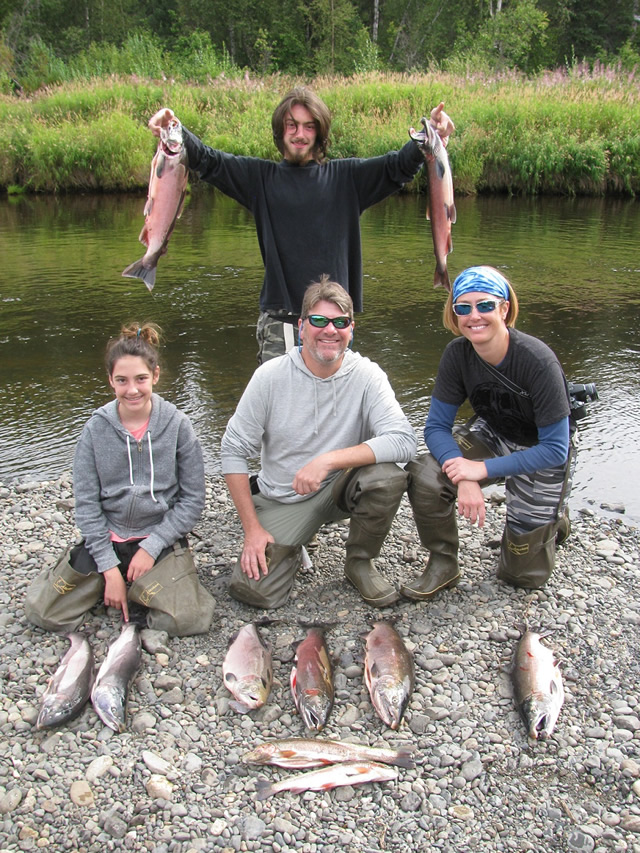 Amelia, Dennis, Sue and Isaac standing in the background show off some of there nice Deshka River silvers.