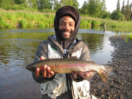Chris holds a beautiful Deshka Rainbow as Adam is fly fishing in the background